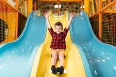 Οδήγηση αγοριών από τις φωτογραφικές διαφάνειες των παιδιών στην παιδική χαρά Στοκ Εικόνα