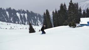 Οδήγηση νεαρών άνδρων Snowboarder στα χιονώδη βουνά ορών, ελβετικά απόθεμα βίντεο