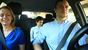 Οδήγηση οικογένειας, mom μπαμπάδων και γιων στο αυτοκίνητο, τραγουδούν τα τραγούδια με ολόκληρη την οικογένεια απόθεμα βίντεο