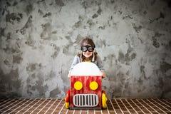 Οδήγηση παιδιών σε ένα αυτοκίνητο φιαγμένο από κουτί από χαρτόνι Στοκ Εικόνες