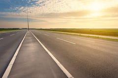 Οδήγηση σε έναν κενό αυτοκινητόδρομο προς τον ήλιο ρύθμισης Στοκ εικόνες με δικαίωμα ελεύθερης χρήσης