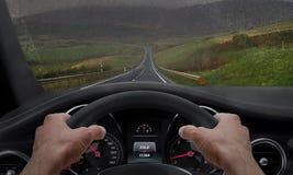 Οδήγηση στο βροχερό καιρό Άποψη από τη γωνία οδηγών ενώ χέρια στη ρόδα Καταβρεγμένος βροχή ανεμοφράκτης Στοκ εικόνα με δικαίωμα ελεύθερης χρήσης