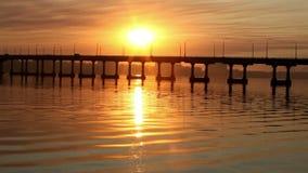 Ο ήλιος αυξάνεται πέρα από τον ποταμό μετά από τη γέφυρα, αντανακλάσεις νερού απόθεμα βίντεο