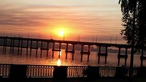 Ο ήλιος αυξάνεται πέρα από τον ποταμό μετά από τη γέφυρα, αντανακλάσεις νερού φιλμ μικρού μήκους