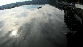 Ο ήλιος αυξάνεται στο κουπί λεμβούχων λιμνών ο τρόπος του προς την ακτή της μολυσμένης λίμνης Σκιαγραφίες φιλμ μικρού μήκους