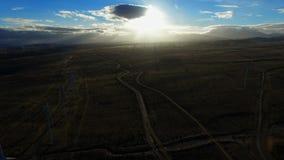 Ο ήλιος λάμπει λαμπρά πέρα από τους ανεμοστροβίλους σε έναν εγκαταλειμμένο τομέα απόθεμα βίντεο