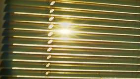 Ο ήλιος λάμπει μέσω στενού του επάνω τυφλών φιλμ μικρού μήκους