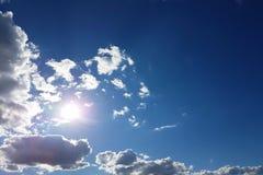 Ο ήλιος λάμπει μέσω των σύννεφων σωρειτών στο μπλε ουρανό Υπόβαθρο και σύσταση για τους καλλιτέχνες και το σχέδιο Φωτεινό φως στα στοκ εικόνα