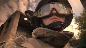 Ο ήρεμος στρατιώτης στο κράνος και την κάλυψη στέκεται sunlights φορώντας γάντια στη μάσκα του ενδεχομένως, κενό σπίτι τούβλου πλ φιλμ μικρού μήκους