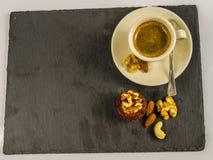 Ο λίγος μαύρος καφές με muffin, τα ξύλα καρυδιάς, τα αμύγδαλα και το ασβέστιο καρυδιών Στοκ Φωτογραφία