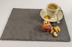 Ο λίγος μαύρος καφές με muffin, τα ξύλα καρυδιάς, τα αμύγδαλα και το ασβέστιο καρυδιών Στοκ εικόνα με δικαίωμα ελεύθερης χρήσης