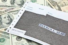 Ολίσθηση μισθοδοτικών καταστάσεων στο σωρό των τραπεζογραμματίων αμερικανικών δολαρίων στοκ εικόνα με δικαίωμα ελεύθερης χρήσης