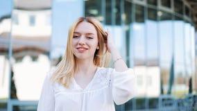 Ο αέρας φυσά την ξανθή τρίχα γυναικών ` s ενώ στέκεται έξω απόθεμα βίντεο