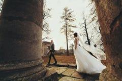 Ο αέρας φυσά το φόρεμα νυφών ` s ενώ περπατά πίσω από καταστρεμμένη cathedr Στοκ Εικόνα