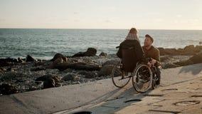 Ο αγαπώντας άνδρας η αναπηρική καρέκλα με τη νέα γυναίκα στην παραλία, να χαρεί απόθεμα βίντεο
