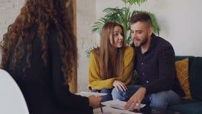 Ο αγαπώντας φίλος και η φίλη εξετάζουν το σχέδιο του σπιτιού που πρόκειται να αγοράσουν και μιλούν στο μεσίτη ακίνητων περιουσιών απόθεμα βίντεο