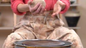 Ο αγγειοπλάστης βάζει ένα κομμάτι του αργίλου στη ρόδα αγγειοπλαστών ` s στο κεραμικό εργαστήριο απόθεμα βίντεο