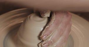 Ο αγγειοπλάστης κάνει την αγγειοπλαστική από στενό επάνω αργίλου Παραγωγή των κεραμικών προϊόντων από τον άσπρο άργιλο Στριμμένη  απόθεμα βίντεο