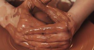 Ο αγγειοπλάστης κάνει την αγγειοπλαστική από στενό επάνω αργίλου Παραγωγή των κεραμικών προϊόντων από τον κόκκινο άργιλο Στριμμέν φιλμ μικρού μήκους