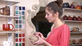Ο αγγειοπλάστης κοριτσιών επιλέγει ένα κατάλληλο χρώμα λούστρου για το φλυτζάνι της από τα διάφορα δείγματα στο εργαστήριο αγγειο απόθεμα βίντεο