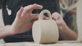 Ο αγγειοπλάστης γυναικών κεραμικής φορμάρει τον άργιλο και κάνει τα μοντέρνα πιάτα φιλμ μικρού μήκους