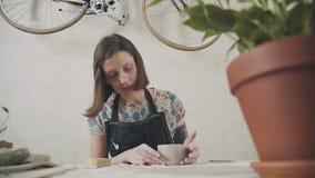 Ο αγγειοπλάστης γυναικών στο στούντιο τέχνης της συμμετέχει στην κατασκευή των κουπών αργίλου φιλμ μικρού μήκους