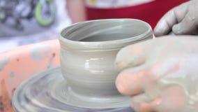 Ο αγγειοπλάστης διδάσκει την τέχνη του στα παιδιά Εργαστήριο κατηγορίας αγγειοπλαστικής Άργιλος που διαμορφώνει στη ρόδα του αγγε απόθεμα βίντεο