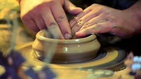 Ο αγγειοπλάστης κάνει τα πιάτα αργίλου Κύρια χέρια που λειτουργούν στη ρόδα αγγειοπλαστών φιλμ μικρού μήκους