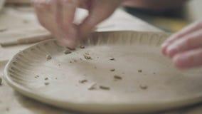 Ο αγγειοπλάστης κάνει το σχέδιο αργίλου στο πιάτο, χρησιμοποιώντας το σωρό φιλμ μικρού μήκους
