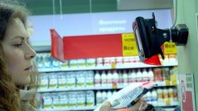 Ο αγοραστής ανιχνεύει τον κώδικα φραγμών στο κατάστημα απόθεμα βίντεο