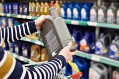 Ο αγοραστής ατόμων επιλέγει το πετρέλαιο για τη μηχανή αυτοκινήτων στο κατάστημα Στοκ Φωτογραφία