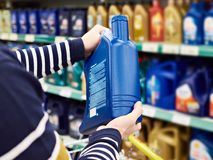 Ο αγοραστής ατόμων επιλέγει το πετρέλαιο για τη μηχανή αυτοκινήτων στο κατάστημα Στοκ Εικόνες