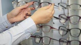 Ο αγοραστής γυναικών αγγίζει τα πλαίσια γυαλιών σε μια στάση σε ένα κατάστημα, κινηματογράφηση σε πρώτο πλάνο φιλμ μικρού μήκους