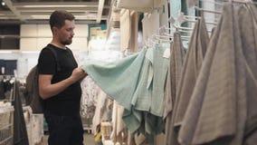 Ο αγοραστής ελέγχει την πετσέτα, την εξετάζει και επιλέγει για το λουτρό απόθεμα βίντεο