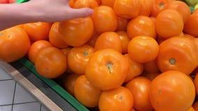 Ο αγοραστής επιλέγει τις φρέσκες κίτρινες ώριμες ντομάτες στην υπεραγορά φιλμ μικρού μήκους