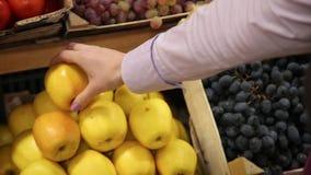 Ο αγοραστής επιλέγει και αγγίζει τα χέρια των μήλων επάνω απόθεμα βίντεο