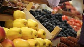 Ο αγοραστής επιλέγει τα μήλα στην αγορά και προσθέτει φιλμ μικρού μήκους
