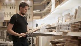 Ο αγοραστής κοιτάζει και κρατά το μεγάλο τέμνοντα πίνακα στη λεωφόρο με το τμήμα επιτραπέζιου σκεύους απόθεμα βίντεο