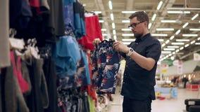 Ο αγοραστής κρατά την κρεμάστρα με τα φωτεινά σορτς στα χέρια και απευθύνεται στο σώμα του απόθεμα βίντεο