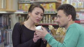 Ο αγοραστής ρωτά κάποιες πληροφορίες στον πωλητή για το προϊόν στο κατάστημα κατοικίδιων ζώων φιλμ μικρού μήκους