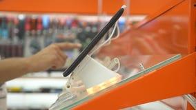 Ο αγοραστής στο κατάστημα ηλεκτρονικής επιλέγει μια νέα συσκευή 4k, κινηματογράφηση σε πρώτο πλάνο, υπόβαθρο θαμπάδων Έρευνα μιας φιλμ μικρού μήκους