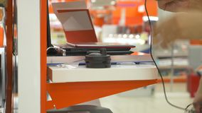 Ο αγοραστής στο κατάστημα ηλεκτρονικής επιλέγει μια νέα συσκευή 4k, κινηματογράφηση σε πρώτο πλάνο, υπόβαθρο θαμπάδων Έρευνα μιας απόθεμα βίντεο