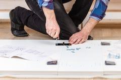 Ο αγοραστής συλλέγει έτοιμος--συγκεντρώνει το δίπλωμα του πίνακα Έτοιμος--συγκεντρώστε τα έπιπλα Εγκατάσταση των εγχώριων επίπλων στοκ εικόνα