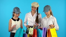 Ο αγοραστής τριών κοριτσιών κοιτάζει στο έγγραφο αγορών bagand και ευτυχής Μπλε υπόβαθρο φιλμ μικρού μήκους