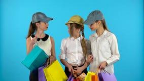 Ο αγοραστής τριών κοριτσιών κοιτάζει στο έγγραφο αγορών bagand και ευτυχής Μπλε υπόβαθρο απόθεμα βίντεο