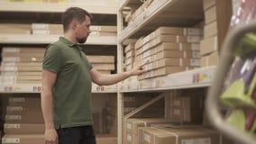 Ο αγοραστής ψάχνει ένα απαραίτητο αγαθό σε μια αποθήκη εμπορευμάτων της οικοδόμησης του καταστήματος απόθεμα βίντεο