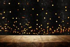 ο αγροτικός ξύλινος πίνακας μπροστά από ακτινοβολεί μαύρα και χρυσά φω'τα bokeh στοκ εικόνες με δικαίωμα ελεύθερης χρήσης
