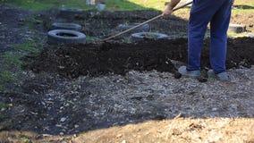 Ο αγρότης κάνει τα κρεβάτια για τη φύτευση των οργανικών και φιλικών προς το περιβάλλον λαχανικών εργασία κήπων φιλμ μικρού μήκους