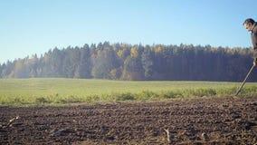 Ο αγρότης χειρίζεται το έδαφος με μια σκαπάνη φιλμ μικρού μήκους