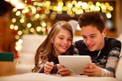 Ο αδελφός και η αδελφή ακούνε μουσική μαζί στις διακοπές Χριστουγέννων Στοκ φωτογραφία με δικαίωμα ελεύθερης χρήσης